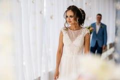 Συνάντηση της νύφης και του νεόνυμφου στο ελαφρύ δωμάτιο Άνδρας πίσω από τη γυναίκα με τα λουλούδια στα χέρια Στοκ φωτογραφίες με δικαίωμα ελεύθερης χρήσης