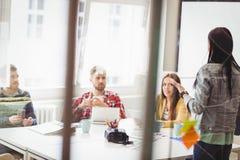 Συνάδελφοι που εξετάζουν τη επιχειρηματία που παρουσιάζει στοκ φωτογραφία