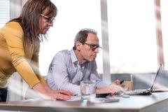 Συνάδελφοι που διοργανώνουν μια επιχειρησιακή συζήτηση, επίδραση ελαφριών ακτίνων Στοκ Εικόνες