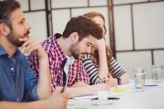 Συνάδελφοι που κάθονται στο γραφείο στο δημιουργικό γραφείο στοκ φωτογραφία με δικαίωμα ελεύθερης χρήσης