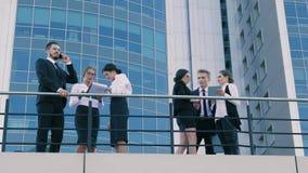 Συνάδελφοι που στέκονται υπαίθρια και που διοργανώνουν την καυτή συζήτηση σχετικά με μια πολυάσχολη εργάσιμη ημέρα φιλμ μικρού μήκους
