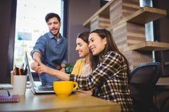 Συνάδελφοι που χαμογελούν δείχνοντας στο lap-top στο γραφείο Στοκ φωτογραφία με δικαίωμα ελεύθερης χρήσης