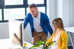 Συνάδελφοι που χρησιμοποιούν την εργασία υπολογιστών στην αρχή στοκ φωτογραφία με δικαίωμα ελεύθερης χρήσης