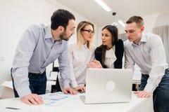 Συνάδελφοι σε μια συνεδρίαση των γραφείων που μιλά και που εργάζεται σε ένα lap-top Στοκ Εικόνα