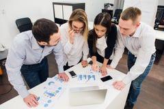 Συνάδελφοι σε μια συνεδρίαση των γραφείων που μιλά και που εργάζεται σε ένα lap-top Στοκ Εικόνες