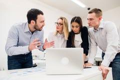 Συνάδελφοι σε μια συνεδρίαση των γραφείων που μιλά και που εργάζεται σε ένα lap-top Στοκ Φωτογραφίες