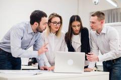 Συνάδελφοι σε μια συνεδρίαση των γραφείων που μιλά και που εργάζεται σε ένα lap-top Στοκ εικόνα με δικαίωμα ελεύθερης χρήσης