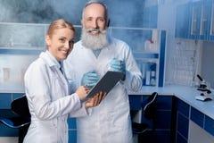 Συνάδελφοι στα παλτά εργαστηρίων που χρησιμοποιούν την ψηφιακή ταμπλέτα κατά τη διάρκεια της εργασίας Στοκ Εικόνες