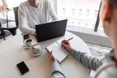Συνέντευξη εργασίας - ο επιτυχής επιχειρηματίας με το lap-top ακούει τις απαντήσεις του υποψηφίου Νέος διευθυντής γυναικών σε μια στοκ φωτογραφία με δικαίωμα ελεύθερης χρήσης