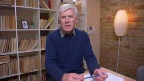 Συνέντευξη του ανώτερου ατόμου που μιλά ήρεμα και κατά τρόπο ενδιαφέροντα στη κάμερα στο υπόβαθρο ραφιών βιβλίων απόθεμα βίντεο
