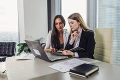 Συνέταιροι ξεκινήματος που εργάζονται μαζί στη νέα συνεδρίαση προγράμματος στο γραφείο που κάνει σερφ Διαδίκτυο που χρησιμοποιεί  στοκ φωτογραφία