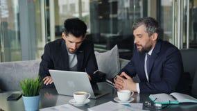 Συνέταιροι που διαπραγματεύονται την ομιλία συμβάσεων που εξετάζει την οθόνη lap-top στον καφέ φιλμ μικρού μήκους