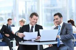 Συνέταιροι που συζητούν ένα νέο πρόγραμμα, που κάθεται στο λόμπι του γραφείου Στοκ φωτογραφία με δικαίωμα ελεύθερης χρήσης