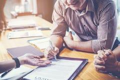 Συνέταιροι που υπογράφουν τη σύμβαση για να δανειστούν τα χρήματα από τον επενδυτή στοκ εικόνες