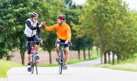Συναγωνιμένος ποδηλάτες μετά από τον αθλητισμό και το δόσιμο υψηλών πέντε Στοκ Εικόνες