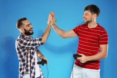 Συναισθηματικά άτομα που παίζουν τα τηλεοπτικά παιχνίδια με τους ελεγκτές στοκ εικόνες με δικαίωμα ελεύθερης χρήσης