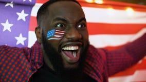 Συναισθηματική κυματίζοντας εθνική σημαία ανεμιστήρων ποδοσφαίρου αφροαμερικάνων, ενθαρρυντική για την ομάδα απόθεμα βίντεο