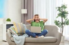 Συναισθηματική νέα γυναίκα με τη νίκη εορτασμού lap-top στον καναπέ στοκ εικόνα με δικαίωμα ελεύθερης χρήσης
