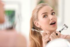 Συναισθηματική νέα γυναίκα με το ρόλερ και τη χτένα eyelash στοκ φωτογραφίες