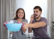 Συναισθηματική νέα γυναίκα που συλλέγει το νερό που διαρρέει από το ανώτατο όριο ενώ ο σύζυγός της που καλεί τον υδραυλικό στοκ εικόνα