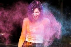 Συναισθηματική τοποθέτηση γυναικών brunette με τη φυσώντας σκόνη Holi Στοκ Εικόνα