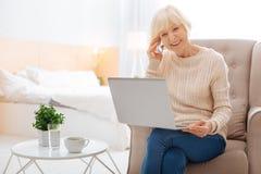 Συναισθηματικός έξυπνος συνταξιούχος που μιλά στο τηλέφωνο καθμένος με ένα lap-top στοκ φωτογραφίες με δικαίωμα ελεύθερης χρήσης
