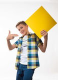 Συναισθηματικός έφηβος αγοριών σε ένα πουκάμισο καρό με το κίτρινο φύλλο του εγγράφου για τις σημειώσεις Στοκ φωτογραφία με δικαίωμα ελεύθερης χρήσης
