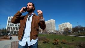 Συναισθηματικός επιχειρηματίας που μιλά irritably στο τηλέφωνο απόθεμα βίντεο