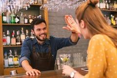Συναισθηματικός μπάρμαν που χαμογελά και που δίνει υψηλά πέντε στον επισκέπτη στοκ φωτογραφία
