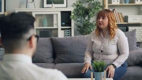 Συναισθηματικός νέος γυναικείος παχύσαρκος ασθενής που συζητά τα προβλήματα με το χαμόγελο θεραπόντων απόθεμα βίντεο