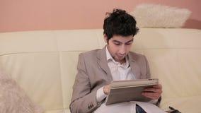 Συναισθηματικός νέος επιχειρηματίας που εργάζεται με την ταμπλέτα φιλμ μικρού μήκους