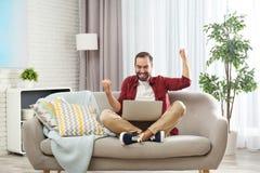 Συναισθηματικός νεαρός άνδρας με τη νίκη εορτασμού lap-top στον καναπέ στοκ εικόνες