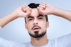 Συναισθηματικός νεαρός άνδρας που πιέζει τις πυγμές του στο μέτωπο και που φαίνεται ανησυχημένος στοκ εικόνα