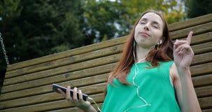 Συναισθηματικός χορός του κοριτσιού εκείνη η μουσική ακούσματος με τα ακουστικά στην ταλάντευση απόθεμα βίντεο