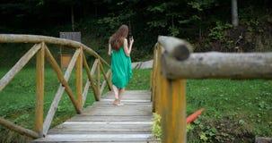 Συναισθηματικός χορός του νέου κοριτσιού στο πράσινο φόρεμα στην ξύλινη γέφυρα απόθεμα βίντεο