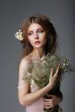 Συναισθηματικότητα. Κοκκινομάλλης στοργική μούσα με τα λουλούδια στα όνειρα Στοκ εικόνα με δικαίωμα ελεύθερης χρήσης