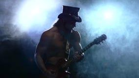 Συναισθηματικό άτομο λουρίδων μυών που παίζει τη βαθιά κιθάρα απόθεμα βίντεο