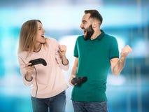 Συναισθηματικό νέο ζεύγος που παίζει τα τηλεοπτικά παιχνίδια με τους ελεγκτές στοκ φωτογραφία