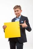 Συναισθηματικό ξανθό αγόρι εφήβων σε ένα κοστούμι με ένα κίτρινο φύλλο του εγγράφου για τις σημειώσεις Στοκ Φωτογραφίες