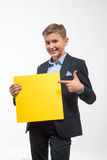 Συναισθηματικό ξανθό αγόρι εφήβων σε ένα κοστούμι με ένα κίτρινο φύλλο του εγγράφου για τις σημειώσεις Στοκ Φωτογραφία