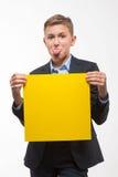 Συναισθηματικό ξανθό αγόρι εφήβων σε ένα κοστούμι με ένα κίτρινο φύλλο του εγγράφου για τις σημειώσεις Στοκ εικόνα με δικαίωμα ελεύθερης χρήσης