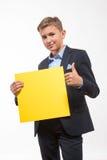 Συναισθηματικό ξανθό αγόρι εφήβων σε ένα κοστούμι με ένα κίτρινο φύλλο του εγγράφου για τις σημειώσεις Στοκ φωτογραφία με δικαίωμα ελεύθερης χρήσης