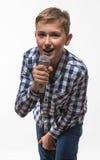 Συναισθηματικό ξανθό αγόρι τραγουδιστών σε ένα πουκάμισο καρό με ένα μικρόφωνο και τα ακουστικά Στοκ Εικόνες