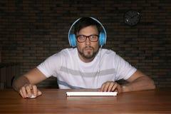Συναισθηματικό παίζοντας παιχνίδι στον υπολογιστή ατόμων στο σπίτι αργά το βράδυ στοκ φωτογραφίες
