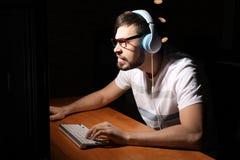 Συναισθηματικό παίζοντας παιχνίδι στον υπολογιστή ατόμων στο σπίτι αργά το βράδυ στοκ εικόνες