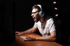Συναισθηματικό παίζοντας παιχνίδι στον υπολογιστή ατόμων στο σπίτι αργά το βράδυ στοκ φωτογραφία με δικαίωμα ελεύθερης χρήσης
