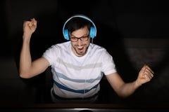 Συναισθηματικό παίζοντας παιχνίδι στον υπολογιστή ατόμων στο σπίτι αργά το βράδυ στοκ εικόνα