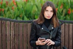 Συναισθηματικό πορτρέτο ενός νέου όμορφου πάρκου πόλεων συνεδρίασης γυναικών brunette υπαίθρια που φορά το μαύρο παλτό δέρματος π Στοκ Εικόνες