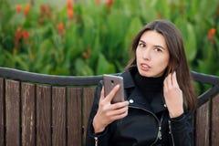 Συναισθηματικό πορτρέτο ενός νέου όμορφου πάρκου πόλεων συνεδρίασης γυναικών brunette υπαίθρια που φορά το μαύρο παλτό δέρματος π Στοκ Εικόνα