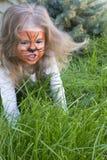 Συναισθηματικό πορτρέτο κινηματογραφήσεων σε πρώτο πλάνο ενός μικρού κοριτσιού με το aqua τιγρών makeup βρυχηθμοί μωρών όπως μια  Στοκ Εικόνες